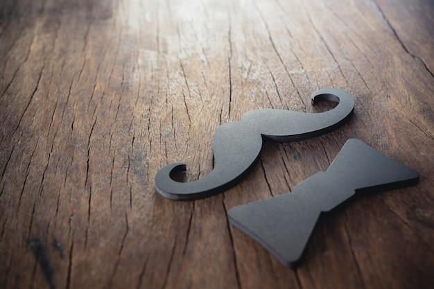 Bigode masculino e laço preto colocados no chão de madeira velho