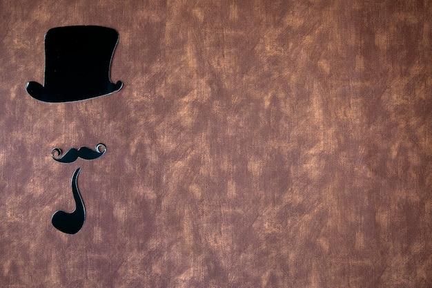 Bigode preto e chapéu em textura de fundo de couro marrom com espaço de cópia, dia internacional do homem e conceito do dia dos pais