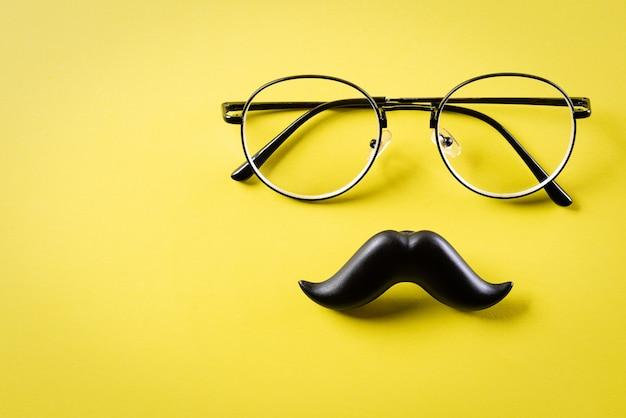Bigode preto e óculos na superfície amarela