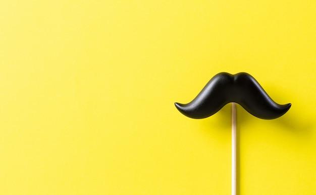 Bigode preto sobre papel amarelo