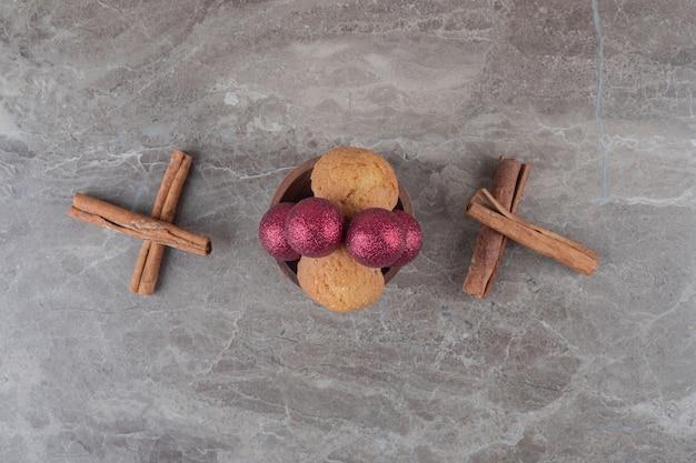 Bijuterias de natal e um biscoito em uma tigela ao lado de paus de canela na superfície de mármore