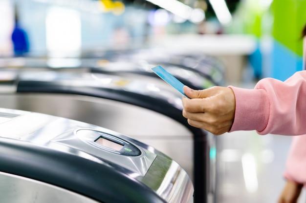 Bilhete de trem da exploração da mão da mulher à porta da entrada do metro. conceito de transporte