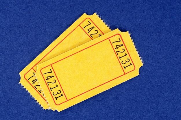 Bilhetes amarelos vazios da admissão em um fundo mottled do papel azul.
