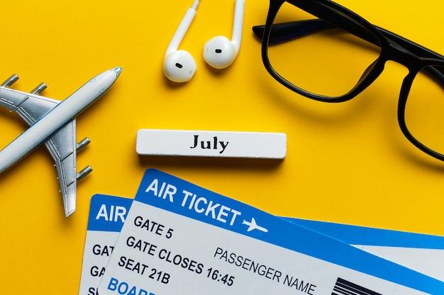 Bilhetes de avião com fones de ouvido e avião em um fundo amarelo