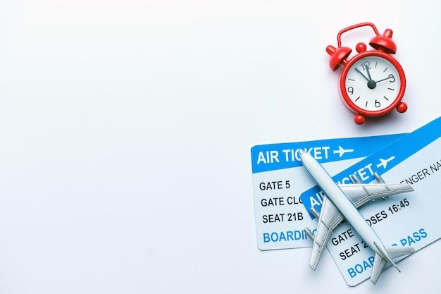 Bilhetes de avião com relógio vermelho sobre um fundo branco