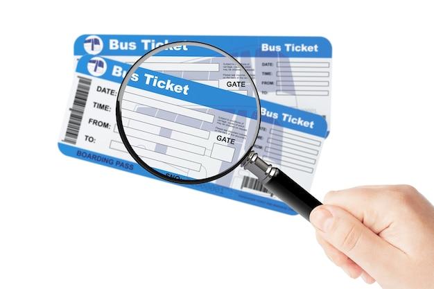 Bilhetes de cartão de embarque de ônibus com lupa na mão em um fundo branco