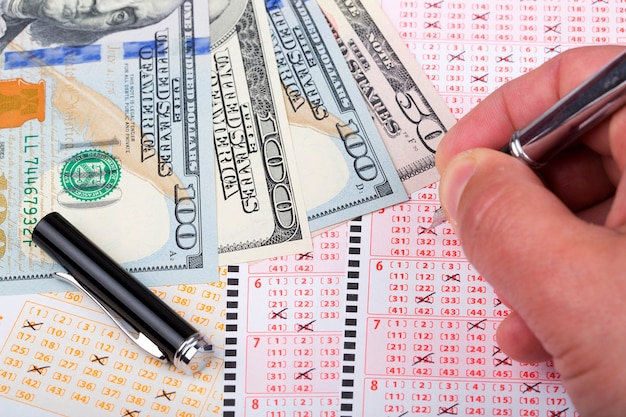 Bilhetes de loteria com uma caneta e dólares americanos