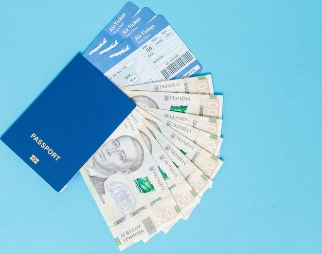 Bilhetes para aviões e passaporte, hryvnia ucraniana sobre um fundo azul. copie o espaço para o texto.