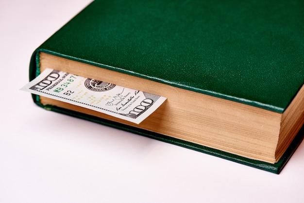 Bill no valor de cem dólares americanos em livro sobre uma macro de fundo branco.