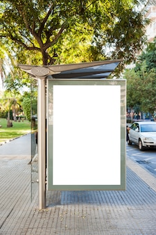 Billboard na parada de ônibus em frente a árvores