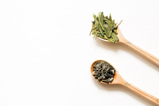 Biluochun e longjing. chá verde da folha chinesa em uma colher em um fundo branco.