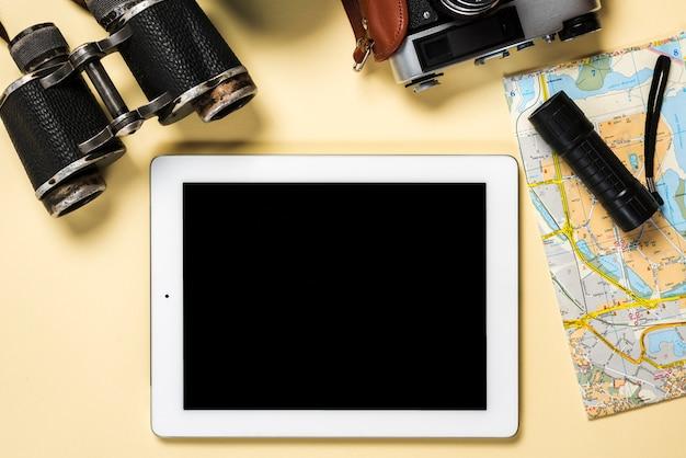 Binocular; câmera; lanterna e mapa com tablet digital mostrando tela preta no pano de fundo bege