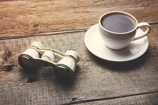 Binóculo e café na mesa de madeira