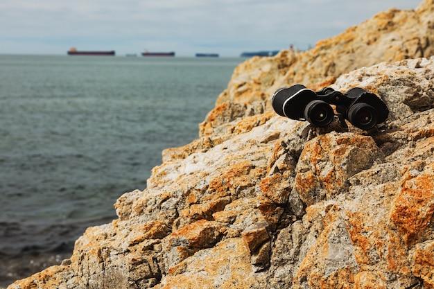 Binóculos antigos nas rochas da costa marítima