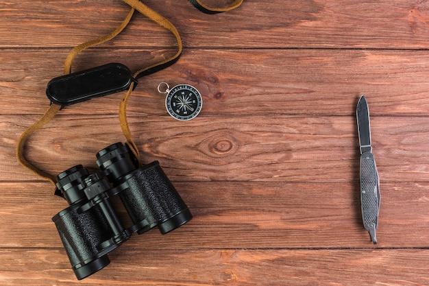 Binóculos, bússola e faca na mesa de madeira