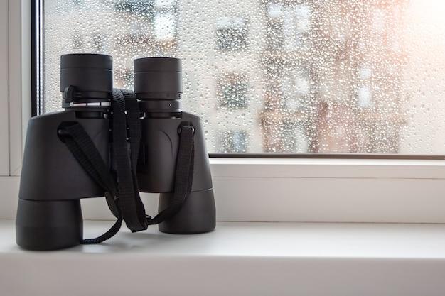 Binóculos no parapeito da janela com gotas de chuva no vidro