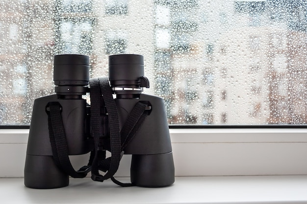 Binóculos pretos no parapeito da janela