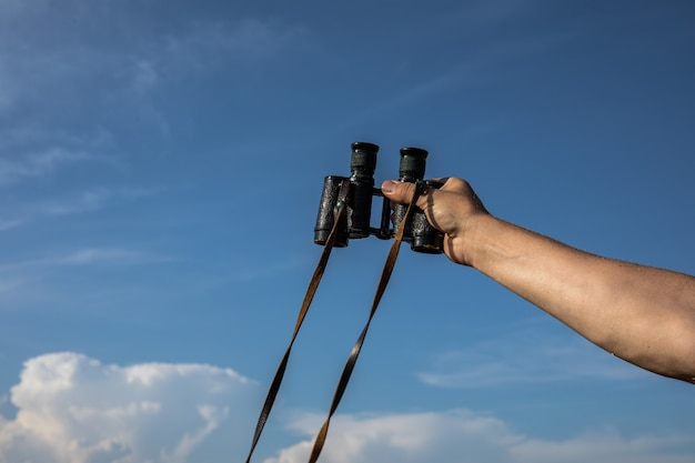 Binóculos velhos na mão, um homem segura os binóculos nas mãos contra o fundo do céu nublado