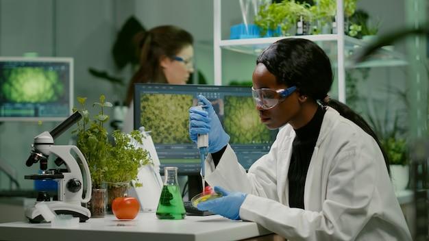 Bióloga cientista mulher africana pesquisadora tirando solução genética de tubo de ensaio