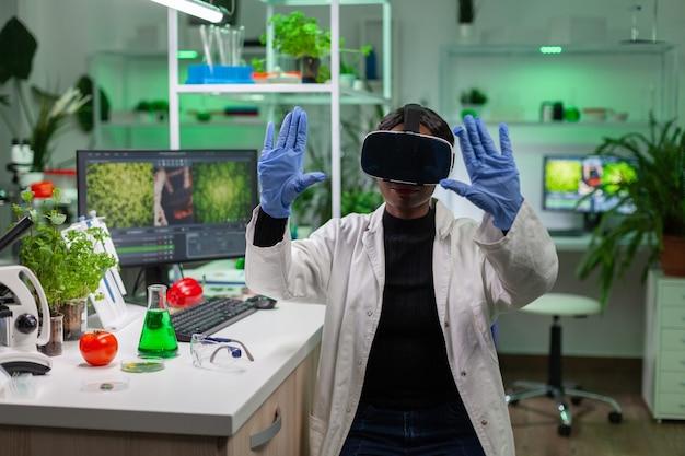 Biólogo cientista africano conduzindo pesquisas usando realidade virtual, fazendo gestos com as mãos para agronomia, olhando para uma amostra. equipe médica trabalhando em laboratório farmacêutico analisando teste de dna.