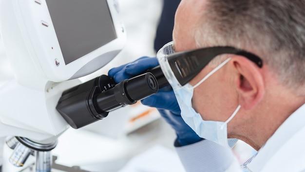 Biólogo cientista com uma máscara protetora olhando através de um microscópio