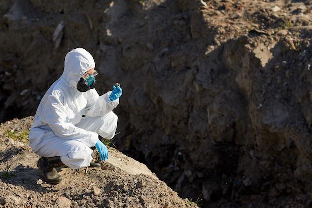 Biólogo com traje de proteção e luvas examinando as amostras de rochas e pedras ao ar livre