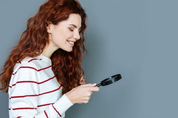 Biólogo profissional. mulher jovem feliz e positiva sorrindo e segurando uma lupa enquanto faz pesquisas biológicas