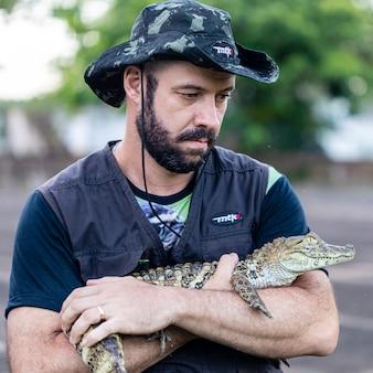 Biólogo segurando um jacaré (caiman latirostris) resgatado com uma pata quebrada