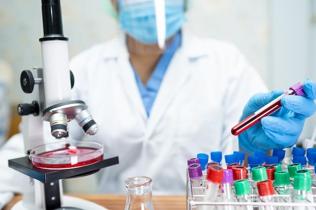 Bioquímico cientista asiático trabalhando em pesquisa com microscópio em laboratório
