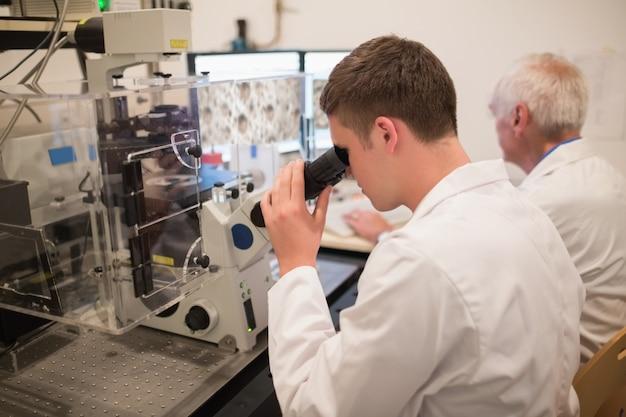 Bioquímico e estudante que olha imagens microscópicas no computador