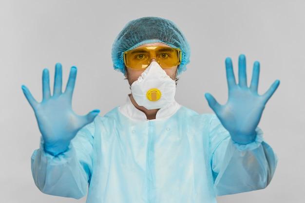 Bioquímico em traje protetor com óculos amarelos, máscara raspiratória e luvas descartáveis azuis com sinal de stop com os braços voltados para a câmera