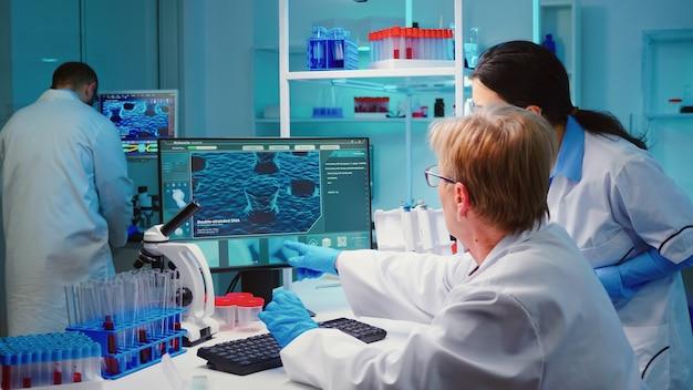 Bioquímico sênior escrevendo no computador as mudanças na composição da vacina em um laboratório equipado e moderno, consultando o colega de trabalho