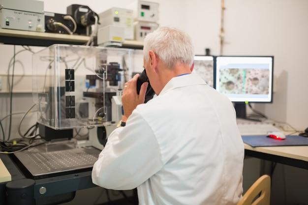 Bioquímico usando grande microscópio e computador
