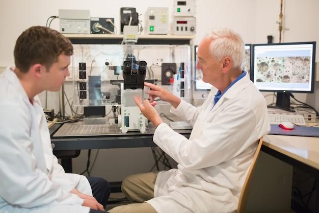 Bioquimista com grande microscópio e computador com aluno