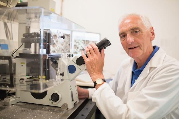 Bioquimista com grande microscópio e computador