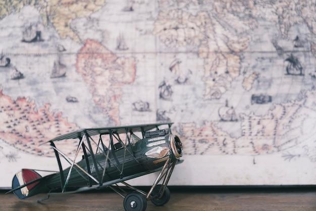 Biplano de brinquedos contra o mapa mundial