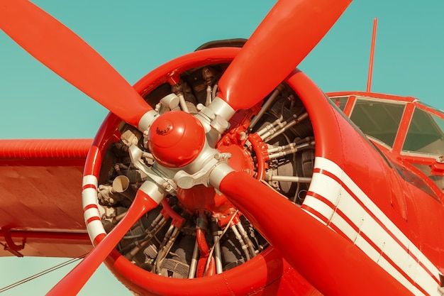 Biplano vermelho no fundo do céu. close-up com motor e hélice
