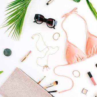 Biquíni de verão feminino e acessórios de colagem em branco com ramos de palmeira, colar e óculos de sol.