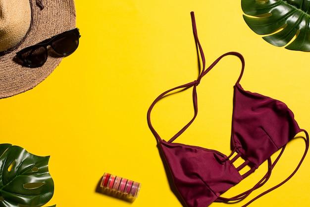 Biquíni, folhas e chapéu amarelo