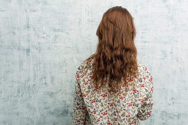 Biquini vestindo da jovem mulher europeia por trás, olhando para trás.