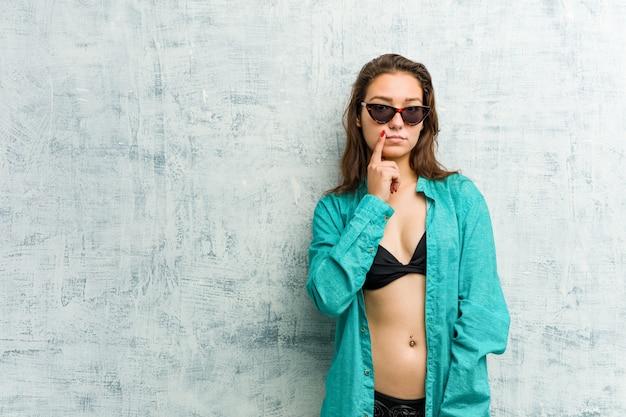 Biquini vestindo da mulher europeia nova que olha lateralmente com expressão duvidosa e cética.
