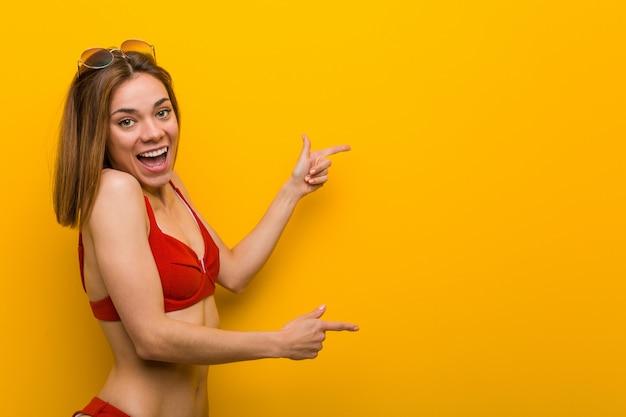 Biquini vestindo e óculos de sol da mulher caucasiano nova excitados apontando com os dedos indicadores ausentes.