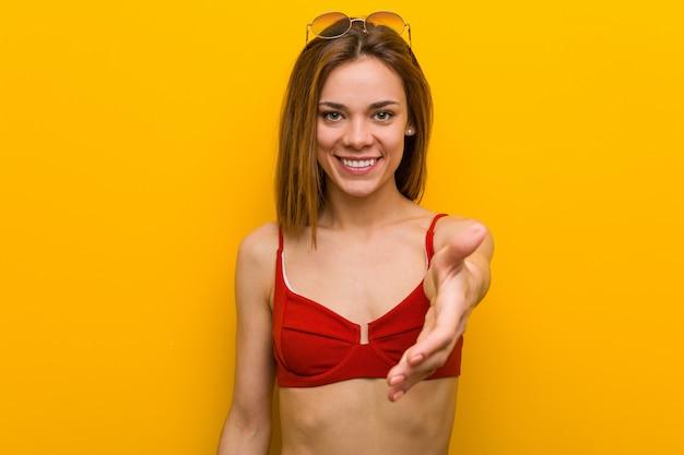 Biquini vestindo e óculos de sol da mulher caucasiano nova que esticam a mão na câmera no gesto do cumprimento.