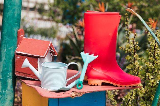 Birdhouse com botas vermelhas wellington; regador; ferramentas de jardinagem no jardim
