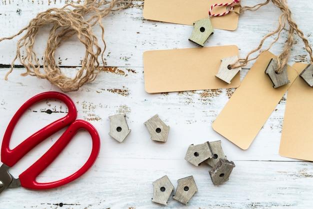 Birdhouses em miniatura; tag; corda e tesoura na mesa branca