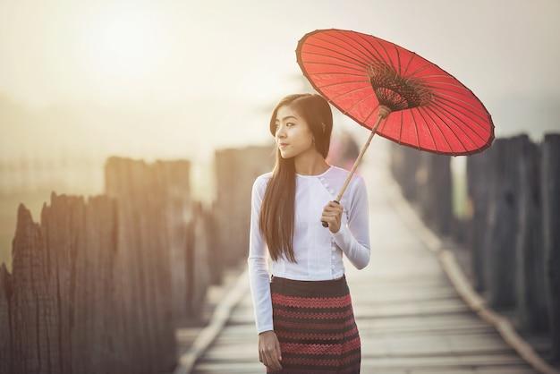 Birmanês, mulheres, em, birmanês tradicional, vestido, com, guarda-chuva vermelho