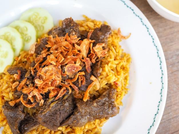 Biryani de carne com chutney verde, arroz amarelo com carne
