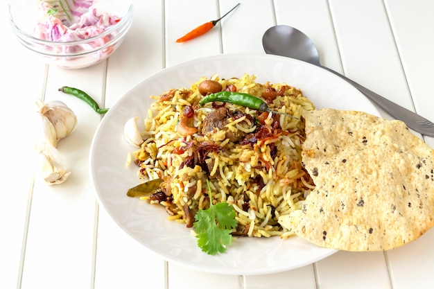 Biryani indiano com acompanhamentos, alhos e pimenta