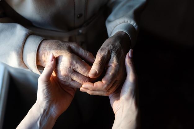Bisavó e neta muito idosas de mãos dadas