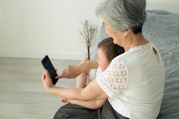 Bisavó senta-se com a bisneta e olha para o smartphone.